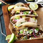 Mexican Lamb Tacos with Tequila Soaked Golden Raisins, Pepitas, and PIckled Onions | sharedappetite.com