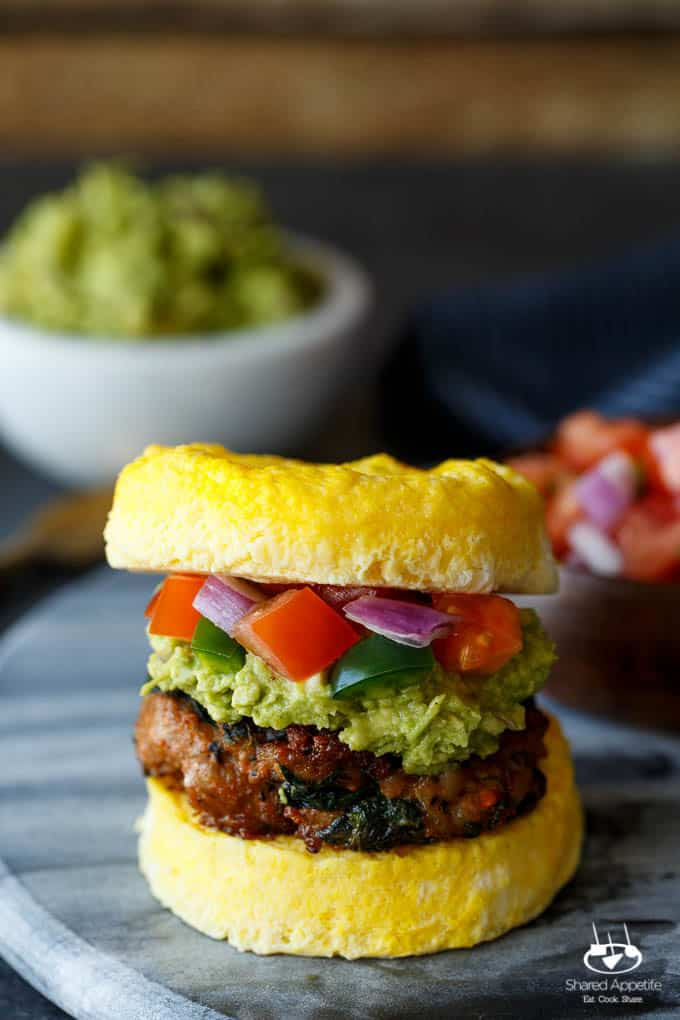 Paleo Southwest Sausage Egg Sandwiches. A healthy Mexican breakfast, using scrambled eggs in place of the bun! Topped with guacamole and pico de gallo, too!