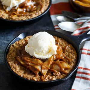Caramel Apple Crisp Pizookies... a giant skillet oatmeal cookie topped with brown sugar baked apples, caramel sauce, and vanilla ice cream! | sharedappetite.com