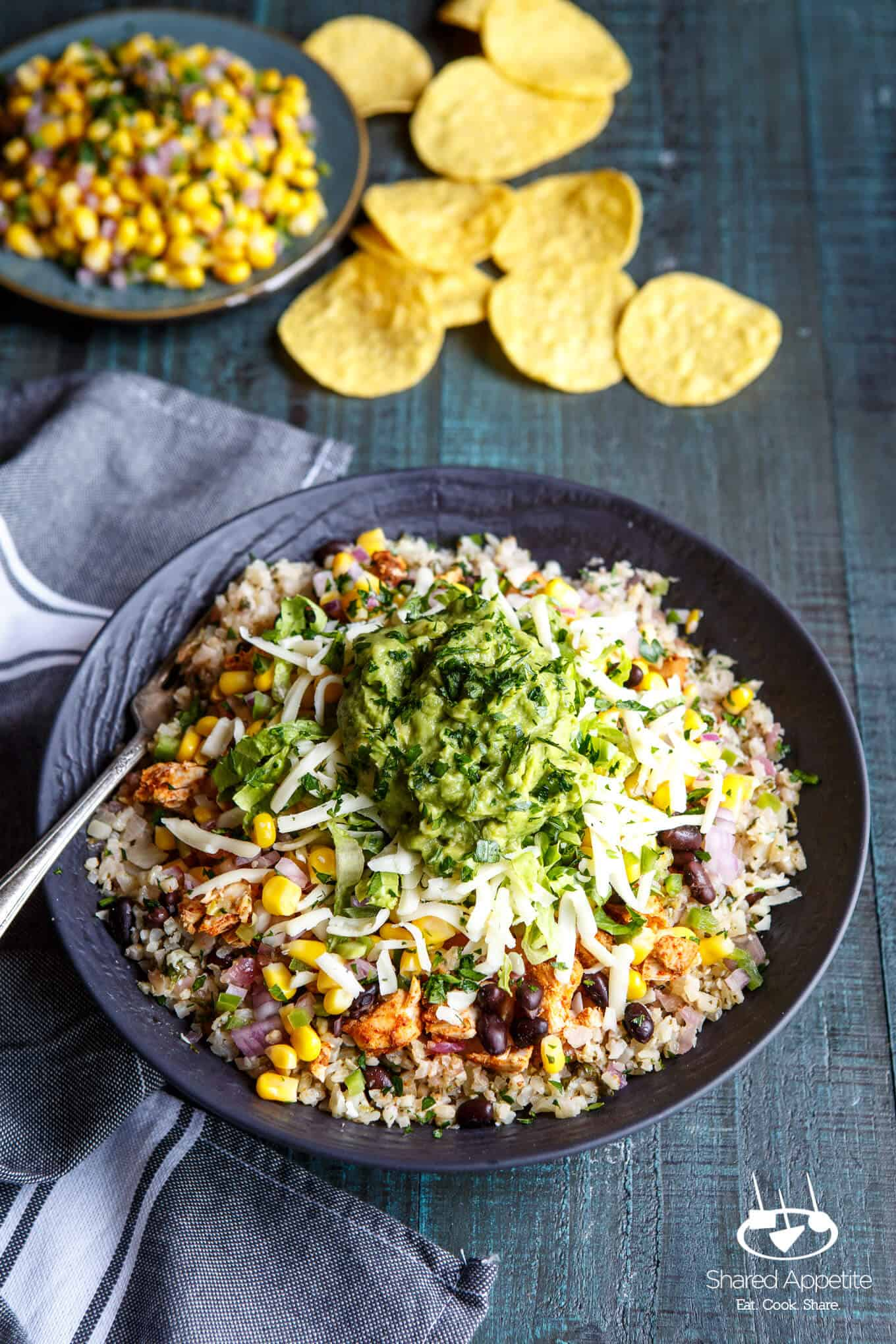 Healthy Cauliflower Rice Burrito Bowls with tortilla chips and corn salsa in the background   sharedappetite.com