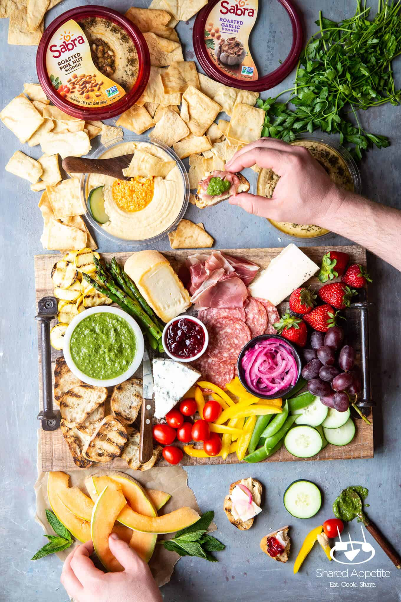 building crostini on a Sabra Hummus for How To Build A Summer Charcuterie Board | sharedappetite.com