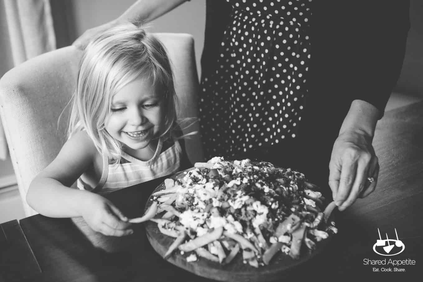 My daughter enjoying these Loaded Mediterranean Lamb Fries | sharedappetite.com